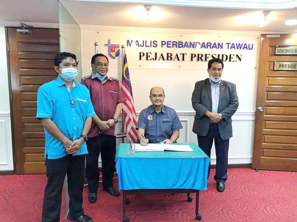 Jamaluddin (duduk) menandatangani buku pelawat MPT.