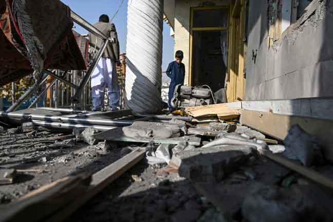 Orang awam memeriksa kerosakan yang disebabkan oleh serangan roket di Khair Khana di Kabul, Afghanistan. — Gambar AFP