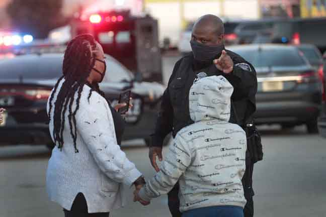 Anggota polis mengarahkan dua orang awam untuk keluar dari kawasan kejadian tembakan di Wauwatosa, Wisconsin. — Gambar AFP