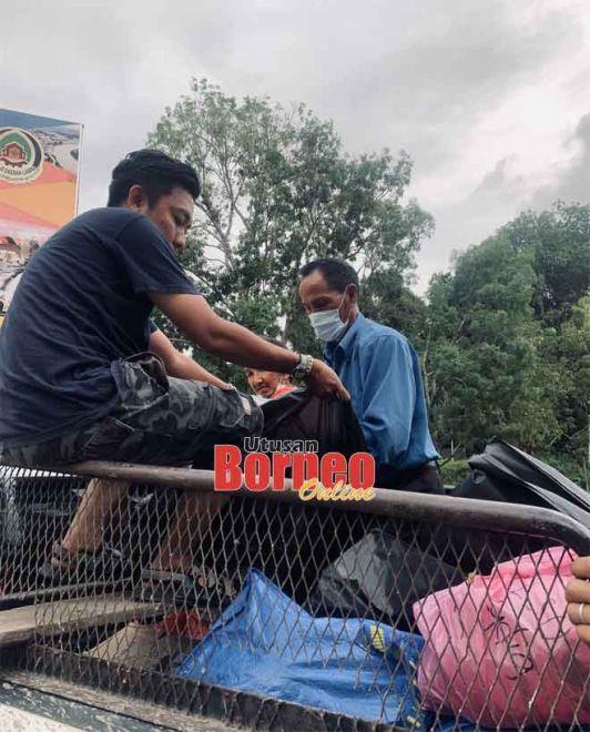 Nazmi (duduk kiri) menumpang kenderaan penduduk yang membawa makanan untuk menghantar lembaran kerja ke rumah murid pedalaman.