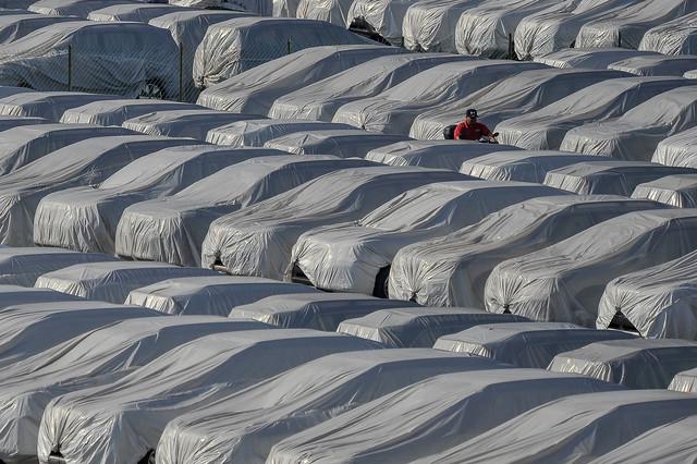 Kelihatan sebahagian kenderaan baru yang ditutup dengan kain kanvas sebelum diedarkan di tempat pengedaran untuk pasaran tempatan hari ini. - Gambar Bernama