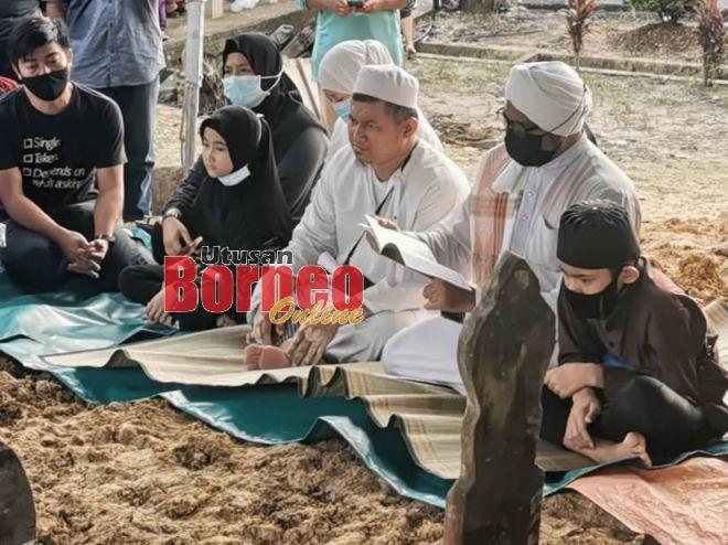 Suami mangsa Hamzah (tiga kanan) dan dua anak sebak dihadapan pusara isteri dan lima anaknya. Gambar Rosytein Emmor