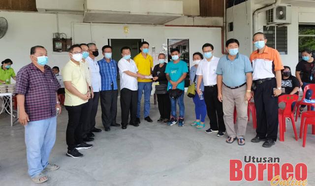 Pengerusi SUPP Sibu Dato Chieng Buong Toon (enam kiri) menyerahkan sumbangan kepada ibu mangsa Munah Agom. Turut kelihatan Hing Ping (lima kanan).