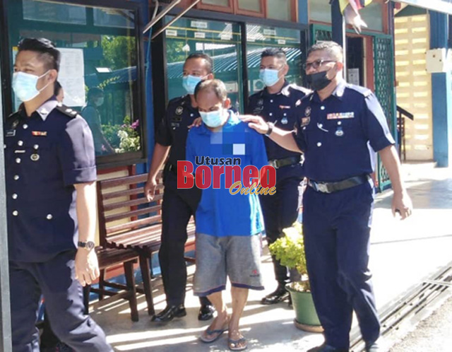 Tertuduh diiringi polis di pekarangan mahkamah hari ini.