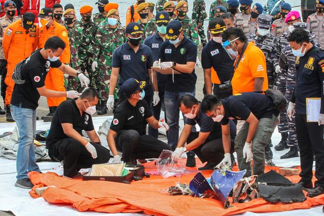 Pekerja penyelamat memeriksa barangan dan puing yang dihantar ke pelabuhan di Jakarta, semalam semasa operasi mencari pesawat Sriwijaya Air yang terhempas kelmarin. — Gambar AFP