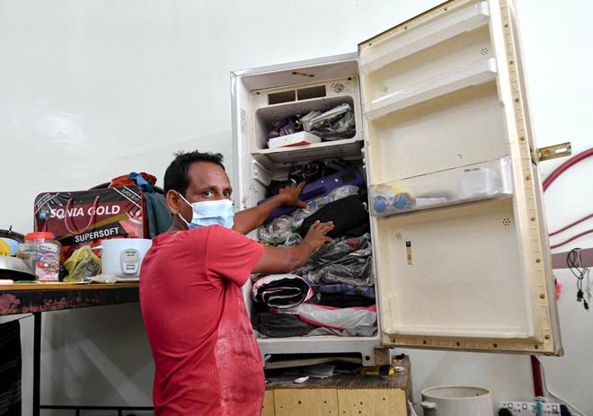 Kalamuddin menunjukkan pakaian yang disimpan di dalam peti ais lama di asrama pekerja sebuah kilang siling ketika Operasi Jabatan Tenaga Kerja (JTK) Perak di sekitar Chemor, Ipoh semalam. — Gambar Bernama
