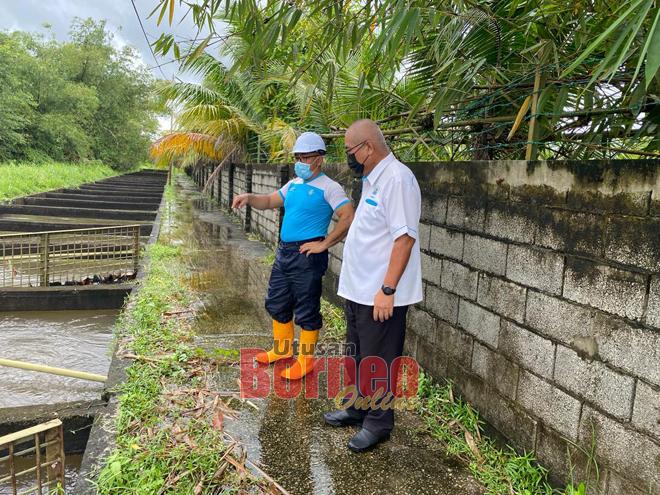 Yii (kanan) memeriksa longkang besar di kawasan Senadin, semalam.