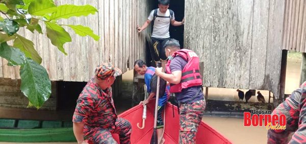 Anggota bomba memindahkan penduduk ke Pusat Pemindahan Banjir di Kg Binsulung Paitan.