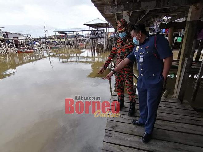 Mohd Hazmin (kanan) dan Zaki menunjukkan lokasi letusan dipercayai minyak mentah di perairan Kampung Awat-Awat, baru-baru ini.