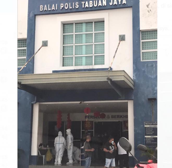 Petugas kesihatan menjalankan ujian calitan di Balai Polis Tabuan Jaya.