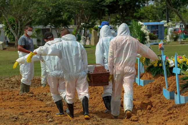 Penggali kubur lengkap berpakaian sut panjang semasa proses pengebumian mayat mangsa wabak COVID-19 di pusat perkuburan Nossa Senhora Aparecida di Manaus, Brazil. — Gambar AFP