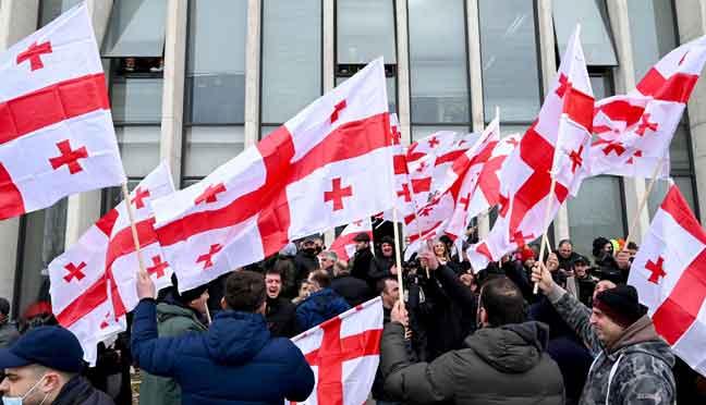 Penyokong pembangkang mengibarkan bendera Georgia sebagai respon pengumuman peletakan jawatan Perdana Menteri Girogi Gakharia di ibu pejabat Pergerakan Bersatu Kebangsaan di Tbilisi. — Gambar AFP