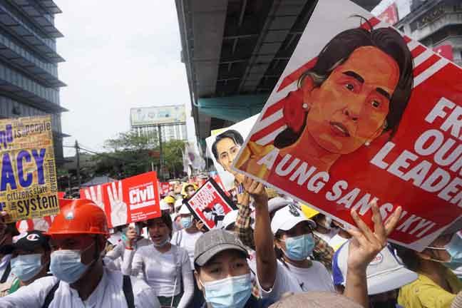 Guru yang menyertai tunjuk perasaan memegang plakad merayu pembebasan Aung San Suu Kyi ketika demonstrasi terhadap junta tentera di Yangon kelmarin.  — Gambar AFP