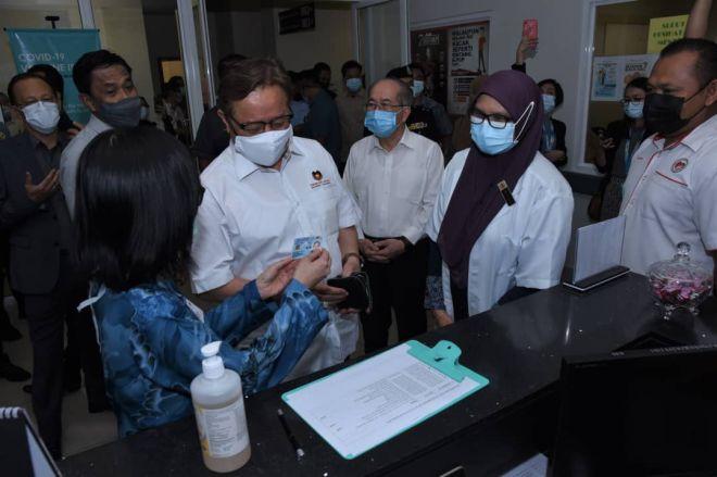 Abang Johari (dua kiri) mendaftar sebelum menerima suntikan vaksin di KK Petra Jaya hari ini. Gambar PENERANGAN