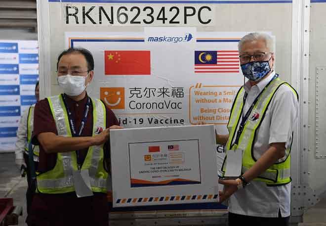 Menteri Kanan (Keselamatan) Datuk Seri Ismail Sabri Yaakob (kanan) menerima kotak bungkusan vaksin Sinovic daripada Ouyang sebagai simbolik penyerahan pada majlis sambutan bekalan kedua vaksin COVID-19 buatan syarikat biofarmaseutikal dari China, Sinovac di Lapangan Terbang Antarabangsa Kuala Lumpur (KLIA), Sepang semalam. Pesawat Airbus 330-300 membawa envirotainer mengandungi vaksin COVID-19 dalam bentuk cecair sebanyak 200 liter itu, mendarat pada kira-kira 9 pagi kelmarin. — Gambar Bernama