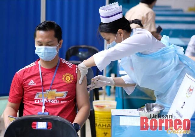 Seorang pertugas barisan hadapan KKM menerima suntikan vaksin COVID-19 di Stadium Perpaduan Kuching, Petra jaya bulan lalu. - Gambar fail