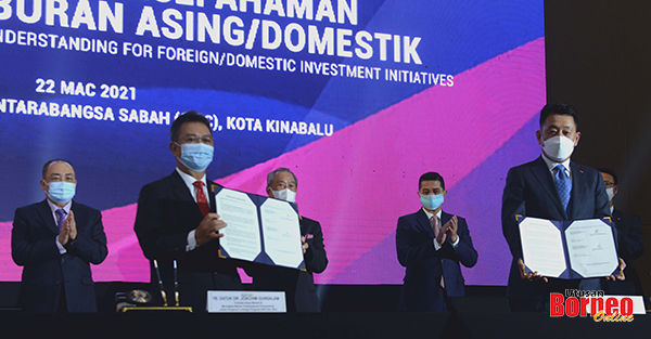 Hajiji (kiri), Muhyiddin (tengah, belakang) menyaksikan pertukaran dokumen MoU ketika dimajlis berkenaan.