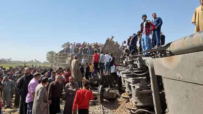 Orang ramai berkumpul berhampiran dua kereta api yang berlanggar di daerah Tahta di selatan Mesir.  — Gambar AFP