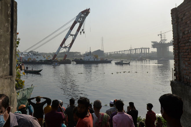 Orang ramai dan sanak saudara mangsa menyaksikan usaha sebuah kapal penyelamat untuk menimbulkan semula feri yang karam di Sungai Shitalakshya di Narayanganj, semalam. — Gambar AFP