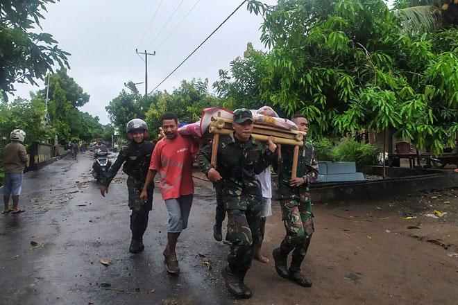Anggota keselamatan mengusung mayat mangsa yang ditemui selepas banjir kilat                  di pulau Lembata, Timor Timur kelmarin. — Gambar AFP