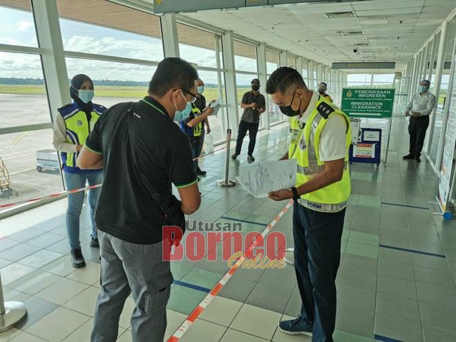 Pegawai dan anggota polis memeriksa dokumen individu yang memasuki Bintulu melalui penerbangan domestik di Lapangan Terbang Bintulu.