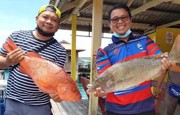 Riduwan dan Zulfahmi bergambar kenangan dengan hasil tangkapan mereka.