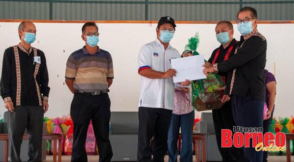 Ewon (tengah) menyampaikan sijil penghargaan dan hamper kepada salah seorang penerima pada majlis itu.