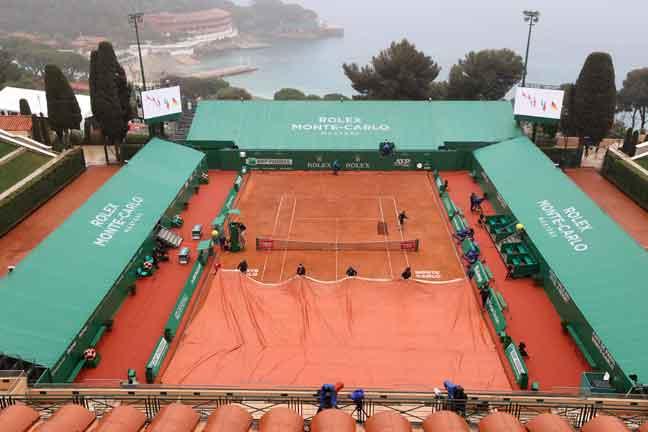 Kakitangan menutup permukaan lantai padang berikutan perlawanan yang ditunda akibat hujan pada kejohanan Monte-Carlo ATP di Monte-Carlo, Monaco, kelmarin— Gambar AFP
