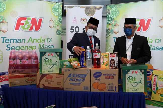 Ahmad melihat barang yang disumbangkan oleh Raffiq (kanan) pada Majlis Pelancaran Kembara Al-Amin Ramadhan 1442H/2021M 'Gerbang Ramadhan Anda' di Kompleks Islam Putrajaya, dekat Putrajaya semalam. — Gambar Bernama
