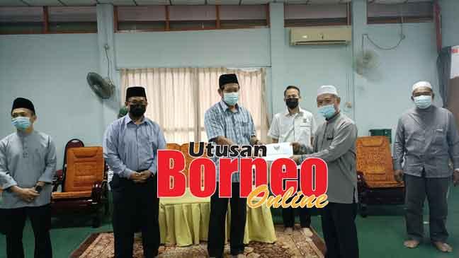 Dr Abdul Rahman (tiga kiba) nyuaka geran nya ngagai Penghulu JAmil Bakar seraya dikemataka Abdul Rahim (kiba), Denney, Superi enggau Penghulu Ahmad Bini (kanan).