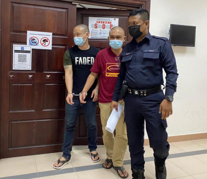 Hanafiah (tengah) bersama Yong (kiri) keluar dari kamar mahkamah selesai dijatuhkan hukuman.