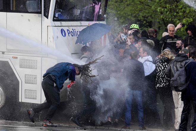 Seorang penunjuk perasaan terkena jet air yang dilepaskan dari meriam semasa bertelingkah dengan polis antirusuhan di taman Bois de La Cambre di Brussels, kelmarin. — Gambar AFP