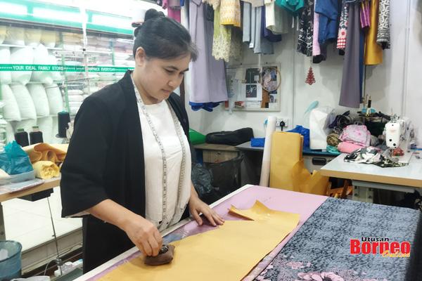 Siti menyiapkan ukuran baju yang ditempah pelanggan di kedainya.