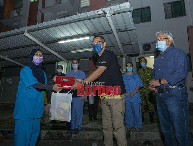 Abdullah dan Samat ketika menyampaikan sumbangan kepada para petugas kesihatan PKRC Kompleks Belia Dan Sukan pada malam Isnin.