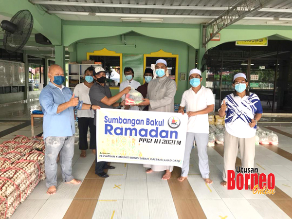 Ustaz Aziz menerima sumbangan daripada Cikgu Darmawan disaksikan beberapa AJK masjid.