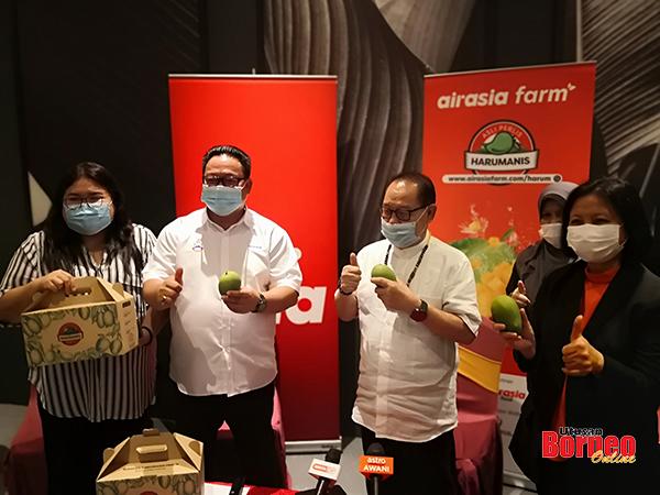 Jeffrey (dua kanan), Hendrus (dua kiri) dan Joanna (kiri) menunjukkan Mangga Harumanis yang memasuki pasaran Sabah