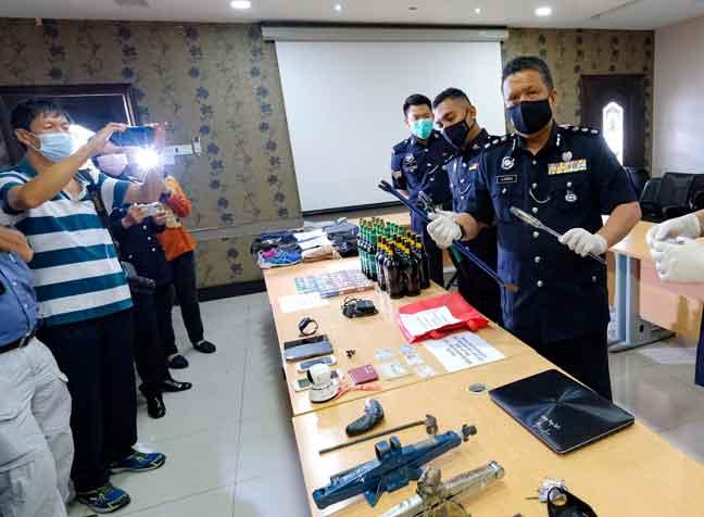 ACP A. Asmadi (kanan) menunjukkan barangan yang dirampas pada sidang media mengenai kes pecah kedai dobi dan kedai runcit di Ibu Pejabat Polis Daerah Ipoh, dekat Ipoh semalam. — Gambar Bernama