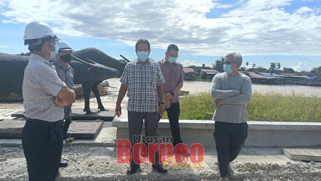 Dr Abdul Rahman (tiga kiri) ketika memantau jalan utama yang rosak berhampiran Projek Tebingan Sungai Fasa Dua semalam.