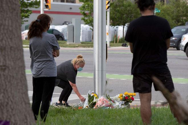 Seorang wanita meletakkan bunga di simpang jalan di mana seorang lelaki memandu trak pikap dengan sengaja melanggar dan menyebabkan kematian empat anggota keluarga Islam di London, Ontario kelmarin. — Gambar AFP
