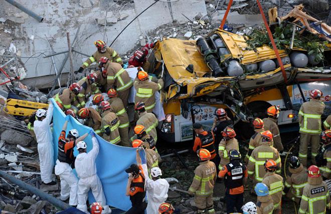 Anggota penyelamat menggeledah runtuhan untuk mencari mangsa terselamat selepas sebuah bangunan yang sedang dalam proses diroboh tiba-tiba runtuh dan menimpa sebuah bas di Gwangju, Korea Selatan kelmarin. — Gambar AFP