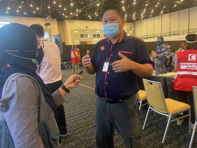 Hwang (kanan) memberi penerangan berkaitan proses vaksinasi. — Gambar Penerangan