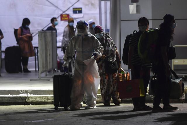 Petugas barisan hadapan membantu membawa beg pesakit COVID-19 semasa menguruskan kemasukan mereka ke PKRC MAEPS. - Gambar Bernama