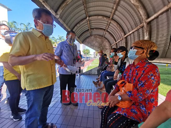 Dr Sim meri penerang ngagai raban orang lunggar umur Flat KMC ti ngena bas maya datai betuchuk vaksin di PPV Klinik Pengerai Tanah Putih. — Gambar Roystein Emmor