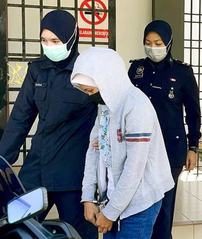 Wanita warga Indonesia diiringi polis selepas selesai prosiding, hari ini. - Gambar Bernama