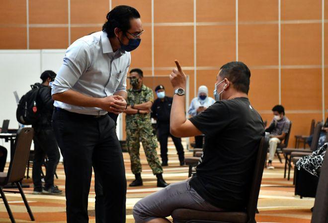 Wan Ahmad Fayhsal beramah mesra bersama penerima vaksin semasa mengadakan lawatan kerja di Pusat Pemberian Vaksin (PPV) Mega Movenpick Hotel dan Pusat Konvensyen, hari ini. - Gambar Bernama