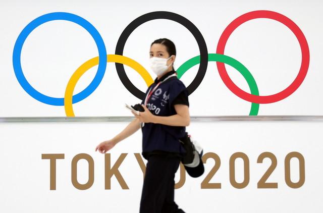 Sukarelawan Sukan Olimpik Tokyo 2020 memakai pelitup muka dan melintasi laluan utama yang menunjukkan logo keramat sukan terbesar dunia itu di bahagian ketibaan utama di Lapangan Terbang Antarabangsa Narita hari ini. - Gambar Bernama