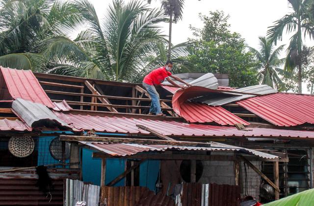 Penduduk kampung membaiki atap yang diterbangkan ribut dalam kejadian berlaku lewat petang semalam di Kampung Nara, hari ini. -Gambar Bernama.
