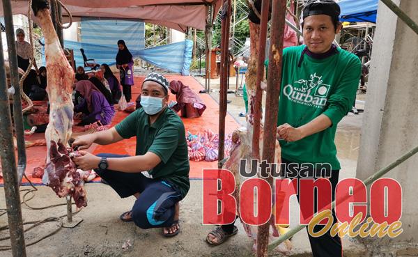 Rosli (kiri) turut membantu melapah daging korban untuk diagihkan kepada golongan asnaf.