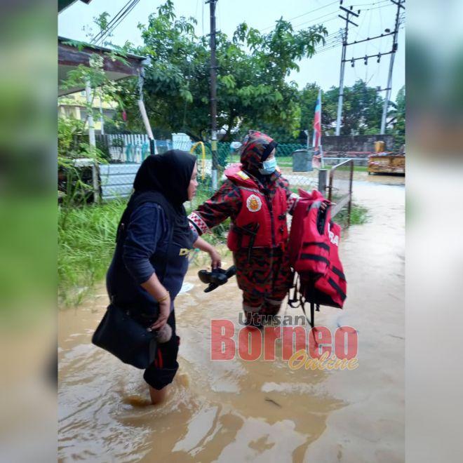 Pasukan bomba membantu memindahkan mangsa banjir ke kawasan selamat.