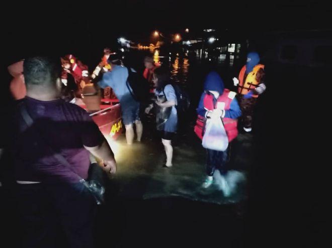 Anggota bomba sedang meninjau dan membantu memindahkan mangsa selepas kediaman mereka dinaiki air banjir kilat malam tadi.